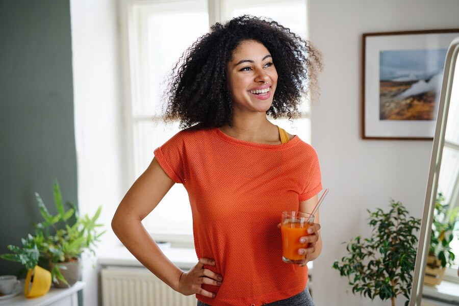 young woman with fair smooth skin holding a healthy drink